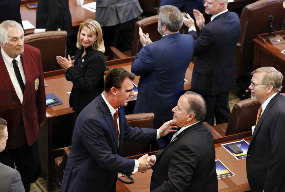 Photo - Gov. Kevin Stitt shakes hands with lawmakers as he leaves the House chamber after his speech. Stitt is shaking the hand of Rep. Lundy Kiger. At right is Rep. Carl Newton. At top of photo looking over her shoulder is Rep. Denise Crosswhite Hader.  Stitt said teachers deserve another pay raise and asked state lawmaker for the money to fund it in his first State-of-the-State address, which he also used to outline his vision for an economy-focused administration that will produce an efficient and adaptive state government. He outlined his plans moving forward in his first term as governor while speaking to lawmakers on Monday, Feb. 4, 2019, as the 57th Legislature officially began.  Photo by Jim Beckel, The Oklahoman.