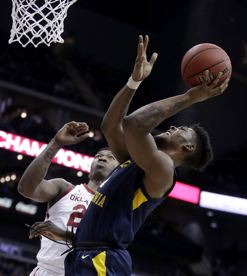 Photo - West Virginia's Derek Culver, front, shoots under pressure from Oklahoma's Kristian Doolittle during the first half of an NCAA college basketball game in the Big 12 men's tournament Wednesday, March 13, 2019, in Kansas City, Mo. (AP Photo/Charlie Riedel)