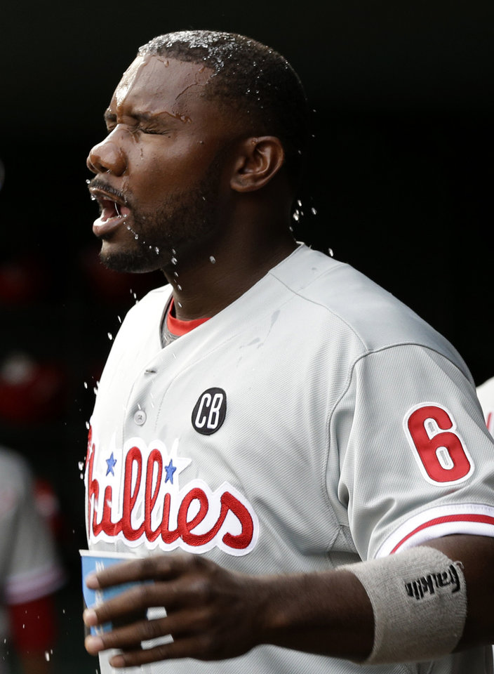 Photo - Philadelphia Phillies' Ryan Howard (6) splashes his face with a cup of water in the first inning of a baseball game against the Texas Rangers, Tuesday, April 1, 2014, in Arlington, Texas. (AP Photo/Tony Gutierrez)