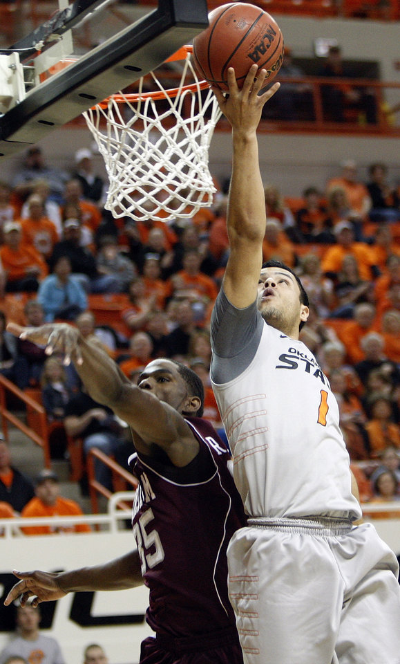 Photo - OSU's Cezar Guerrero (1) lays in a shot over Texas A&M's Ray Turner (35) in the first half of a men's college basketball game between the Oklahoma State University Cowboys and Texas A&M University Aggies at Gallagher-Iba Arena in Stillwater, Okla., Saturday, Feb. 25, 2012. OSU won, 60-42. Photo by Nate Billings, The Oklahoman