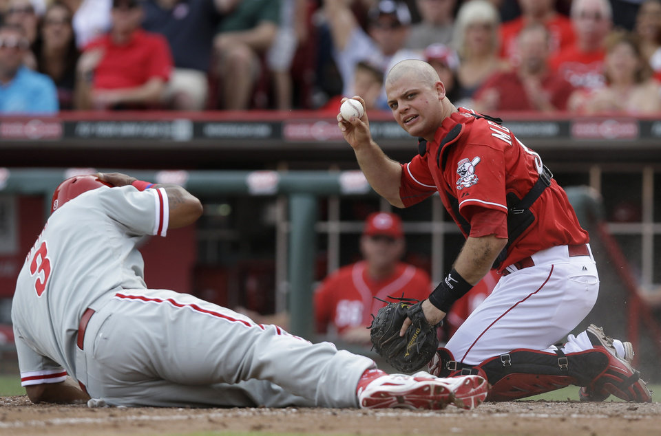 Photo - Cincinnati Reds catcher Devin Mesoraco holds up the ball after tagging out Philadelphia Phillies' Marlon Byrd (3) at home in the sixth inning of a baseball game, Saturday, June 7, 2014, in Cincinnati. Byrd was trying to score on a double by Domonic Brown. (AP Photo/Al Behrman)
