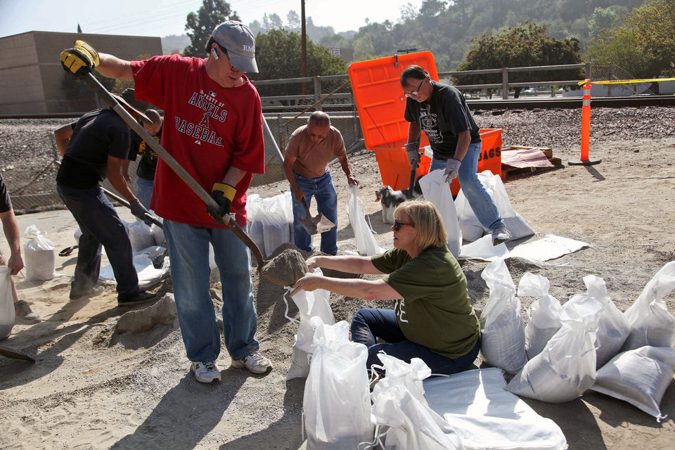 Photo - Mark and Barbara Albanese fill sand bags to protect their home from the possible flooding ahead of an expected rain storm in Azusa,Calif. on Tuesday, Feb 25, 2014. In anticipation of the first substantial winter storm system in drought-stricken California, residents of foothill communities picked up sandbags at fire stations and city yards to protect their homes on Tuesday. (AP Photo/Nick Ut )