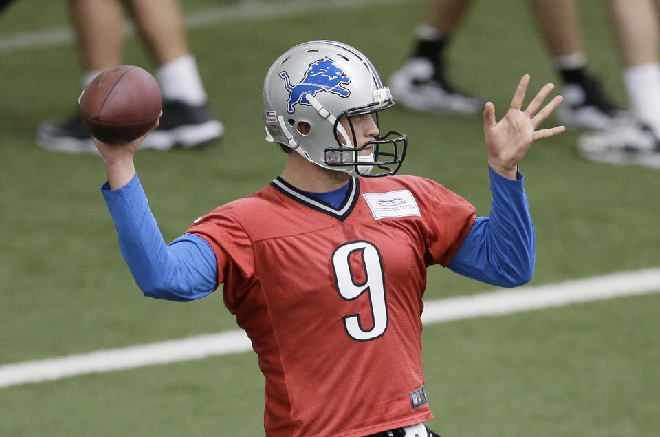 Photo - Detroit Lions quarterback Matthew Stafford runs through drills at the Lions training facility in Allen Park, Mich., Tuesday, April 22, 2014. (AP Photo/Carlos Osorio)