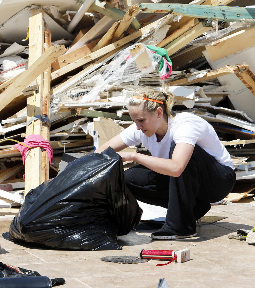 Cheyenne Wiley, 18, sorts through items gathered from the remains of her home on Thursday, May 23, 2013 in Little Axe, Okla.  The house was destroyed in Sunday's tornado in the Woodlands and Pecan Valley area.  Cheyenne lost all her clothes and her cap and gown for her graduation on Tuesday.   Photo by Steve Sisney, The Oklahoman