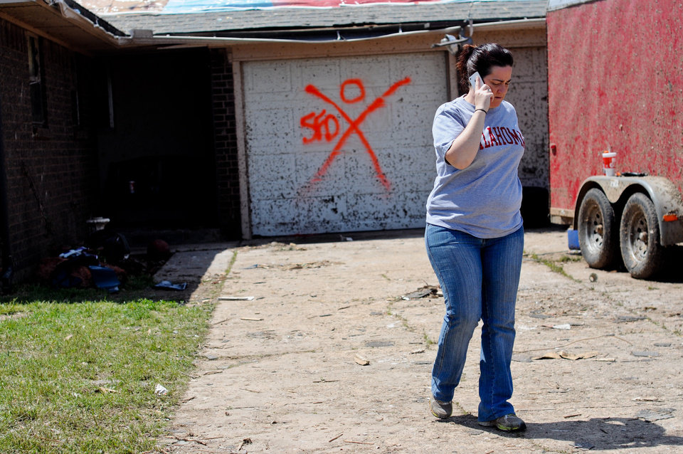 Photo - Summer Roberts walks down the driveway from her home while talking to friends and family who are volunteering their time to help the family.  Photo by KT King, The Oklahoman