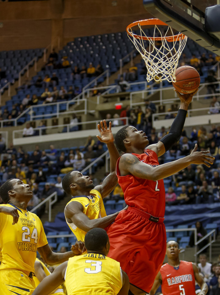 Radford\'s Javonte Green (2) goes in for a layup past West Virginia\'s Aaric Murray (24), Jabarie Hinds, center, and Juwan Staten (3) during the first half of an NCAA college basketball game at WVU Coliseum in Morgantown, W.Va., Saturday, Dec. 22, 2012. (AP Photo/David Smith)