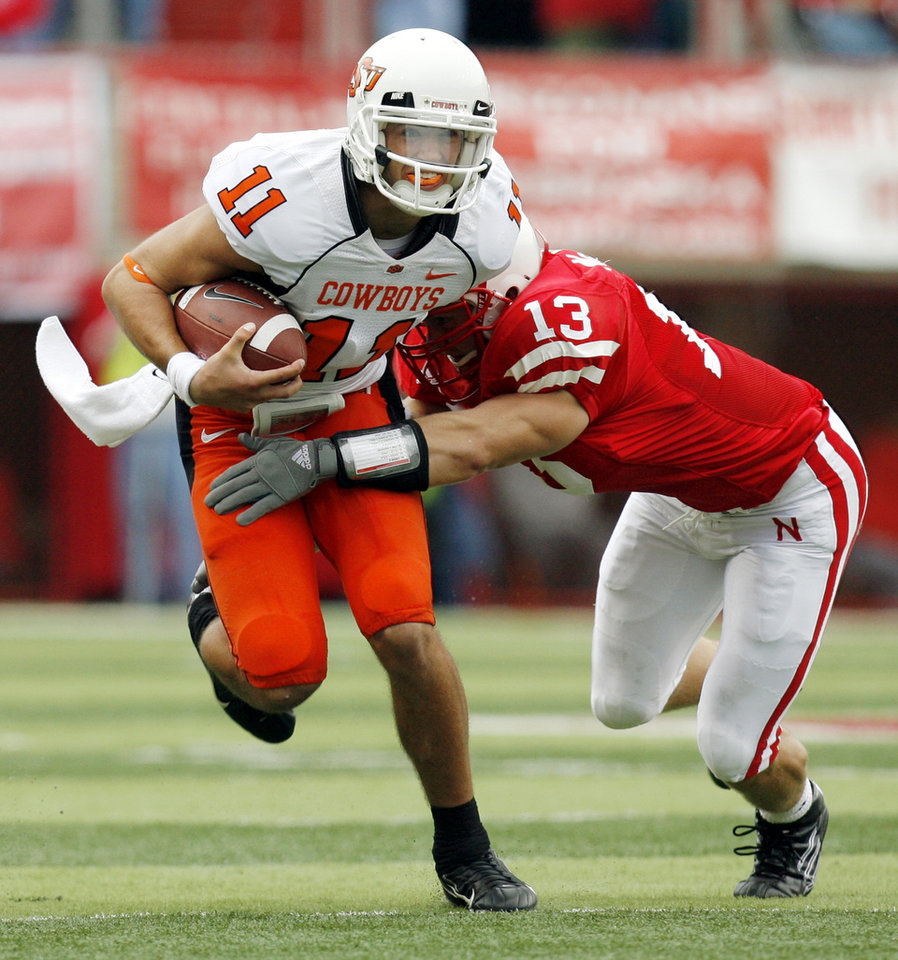 Photo - OSU quarterback Zac Robinson (11) tries to break away from Nebraska's Corey McKeon (13) on a keeper during the college football game between Oklahoma State University (OSU) and the University of Nebraska (NU) at Memorial Stadium in Lincoln, Neb., Saturday, October 13, 2007. OSU won, 45-14. By Nate Billings, The Oklahoman