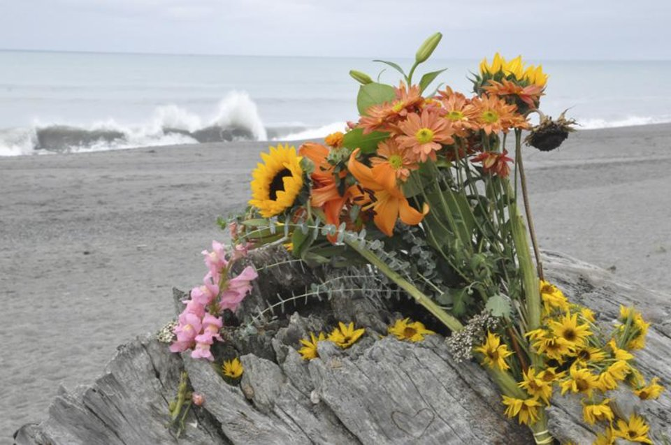 Photo - Flowers are rest on a large drift log yards from the breaking surf of the Big Lagoon beach near Trinidad, Calif. on Monday, Nov. 26, 2012. A family that tried to rescue their dog from powerful surf at the beach in Northern California were swept out to sea, leaving the parents dead and their 16-year-old son missing, authorities said. (AP Photo/The Times-Standard, Jose Quezada)