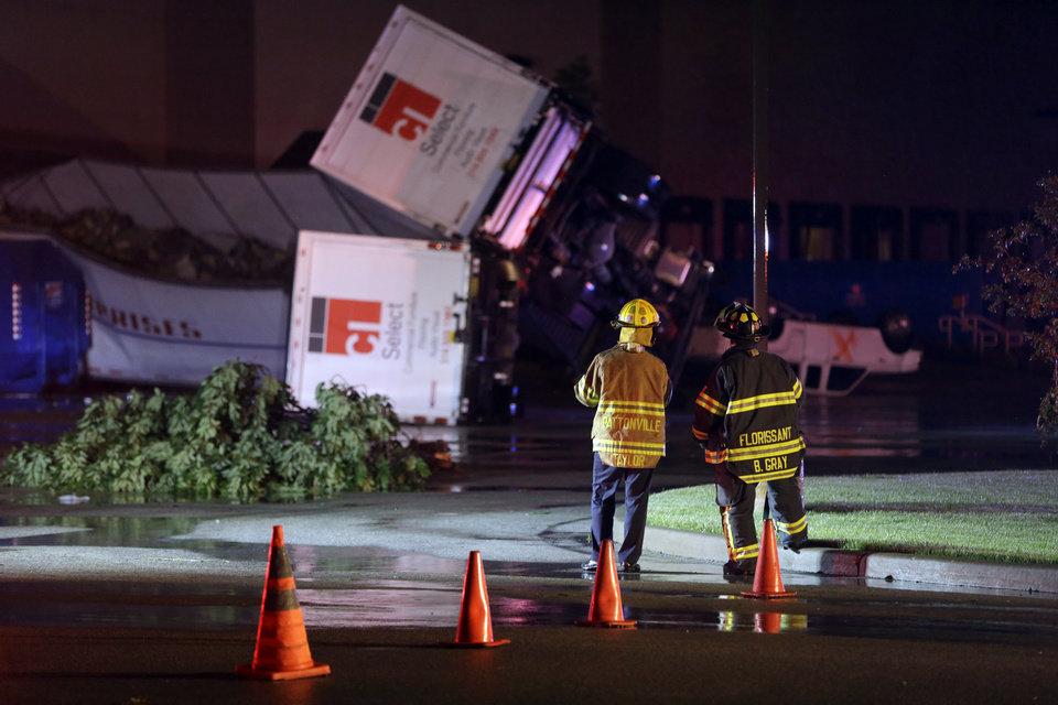 Rescue personnel stand near overturned trucks in an industrial park after strong storms moved through the area Friday, May 31, 2013, in St. Louis. (AP Photo/Jeff Roberson)