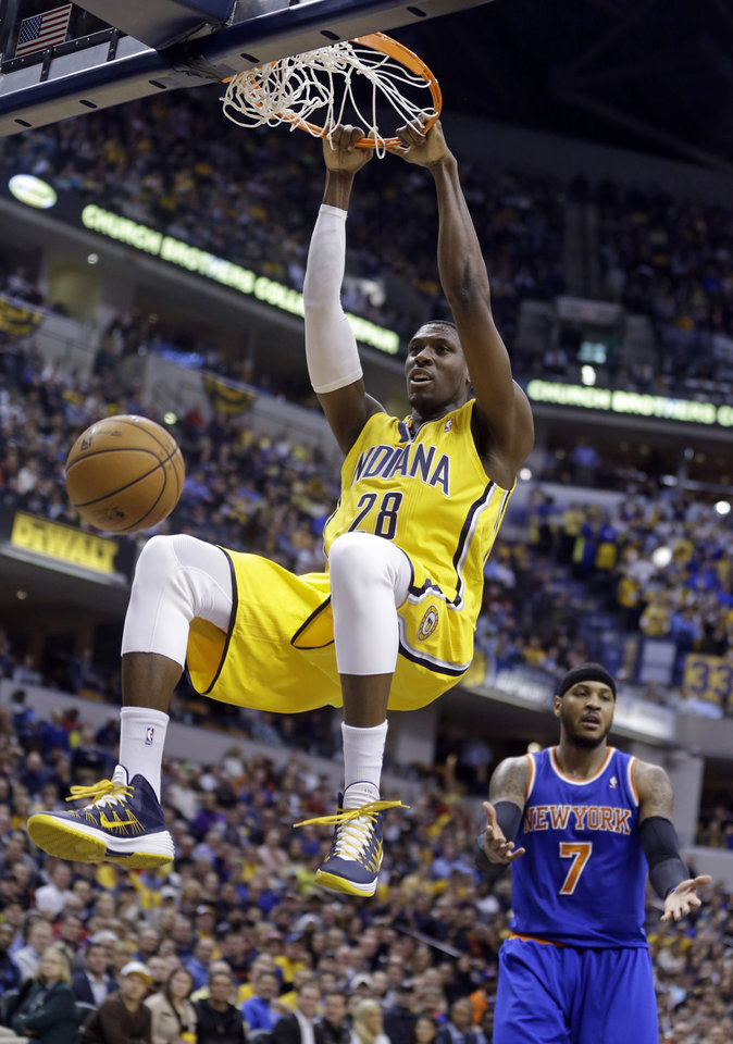 Photo - Indiana Pacers center Ian Mahinmi (28) gets a dunk in front of New York Knicks forward Carmelo Anthony during the second half of an NBA basketball game in Indianapolis, Thursday, Jan. 16, 2014. The Pacers defeated the Knicks 117-89. (AP Photo/Michael Conroy)