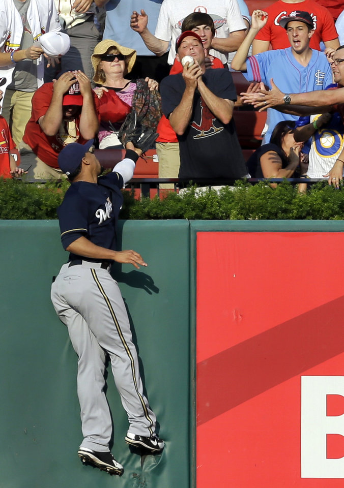 Photo - Milwaukee Brewers center fielder Carlos Gomez climbs the outfield wall as a fan catches a solo home run by St. Louis Cardinals' Kolten Wong during the first inning of a baseball game Saturday, Aug. 2, 2014, in St. Louis. (AP Photo/Jeff Roberson)