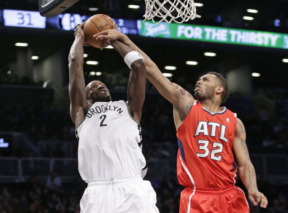 Photo - Atlanta Hawks forward Mike Scott (32) fouls Brooklyn Nets forward Kevin Garnett (2) in the first half of their NBA basketball game at the Barclays Center, Monday, Jan. 6, 2014, in New York. (AP Photo/Kathy Willens)