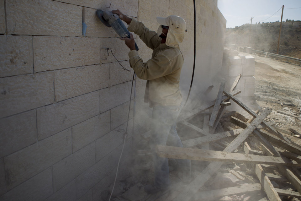 Photo - A Palestinian man works at a new housing development in the Jewish West Bank settlement of Maaleh Adumim, near Jerusalem, Sunday, Dec. 2, 2012. Israel on Sunday roundly rejected the United Nations' endorsement of an independent state of Palestine, and announced it would withhold more than $100 million owed to the Palestinians in retaliation for their successful statehood bid. Israel has a master plan to build 3,600 apartments and 10 hotels on the section of territory east of Jerusalem known as E1. The Palestinians have warned that such construction would kill any hope for the creation of a viable state of Palestine. (AP Photo/Ariel Schalit)