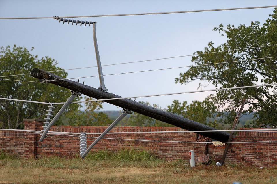 Photo - A utility pole hangs over a brick wall near NW 164 and MacArthur Boulevard in Oklahoma City after storms moved through the area on Tuesday, August 7, 2012. Photo by Bryan Terry, The Oklahoman