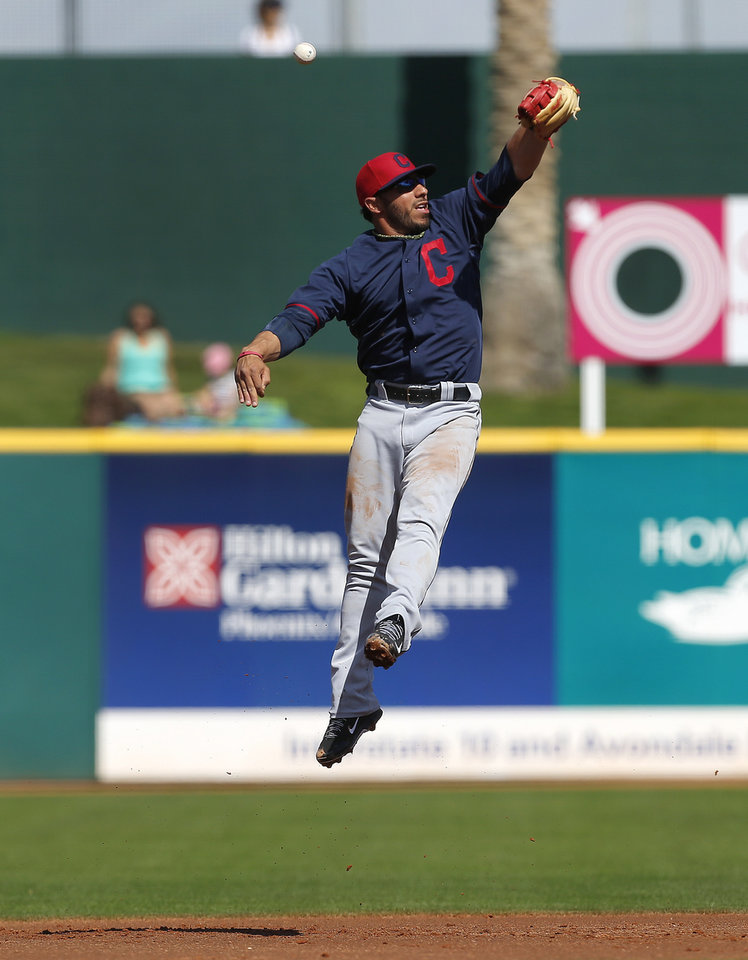 Photo - Cleveland Indians shortstop Mike Aviles jumps but can't catch a Cincinnati Reds hit in the first inning of during an exhibition baseball game in Goodyear, Ariz., Thursday, Feb. 27, 2014. (AP Photo/Paul Sancya)