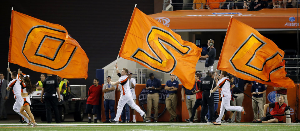 Photo - The Oklahoma State cheer squad run with the flags after a Cowboy's touchdown during the college football game between Oklahoma State University (OSU) and Florida State University (FSU) at the AdvoCare Cowboys Classic at AT&T Stadium in Arlington, Texas on Saturday, Aug. 30, 2014. Photo by Chris Landsberger, The Oklahoman