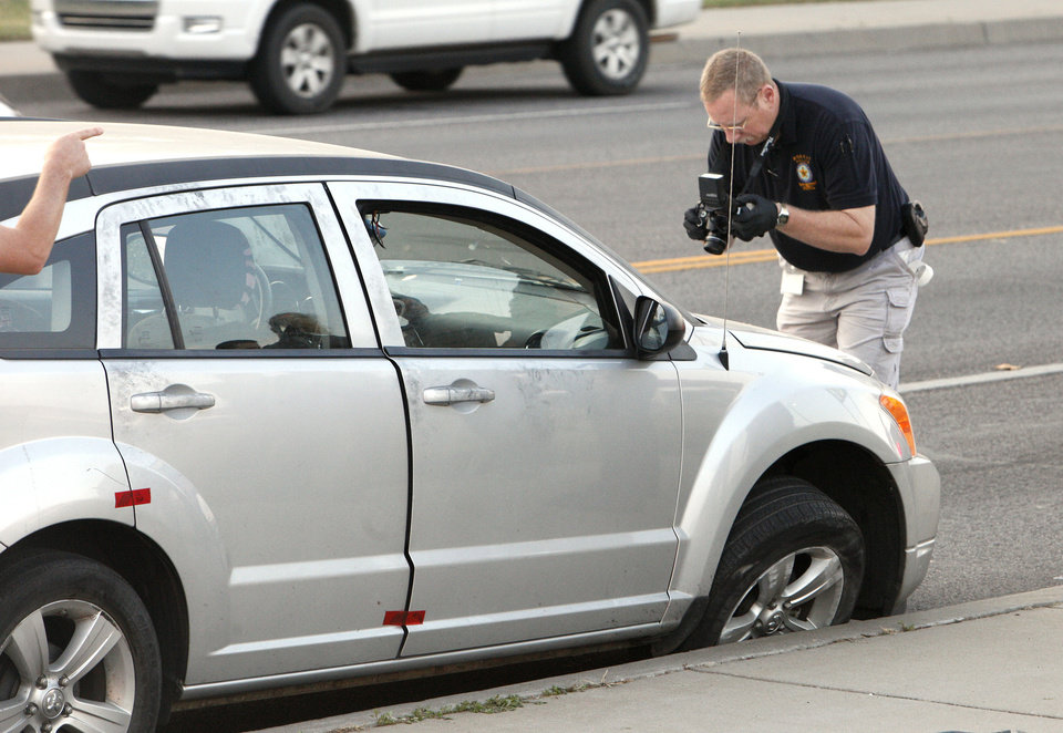 Photo - A Norman Police Department investigator takes photos of a car involved in a Norman shooting that was stopped in south Oklahoma City on May Ave. near SW 67 Street Thursday, Sept. 13, 2012. Photo by Paul B. Southerland, The Oklahoman  PAUL B. SOUTHERLAND - PAUL B. SOUTHERLAND