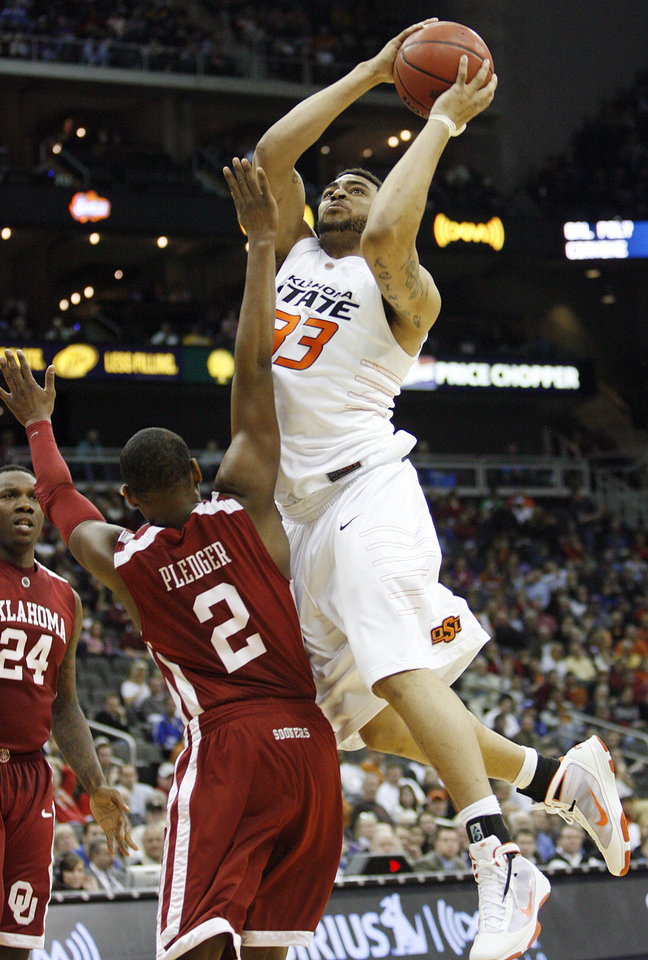 Photo - Oklahoma State's Marshall Moses (33) goes over the top os Oklahoma's Steven Pledger (2) in the second half of the college basketball game during the men's Big 12 Championship tournament at the Sprint Center on Wednesday, March 10, 2010, in Kansas City, Mo. Photo by Chris Landsberger, The Oklahoman