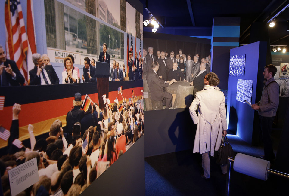 Photo -   A man and a woman look at photos of US President Ronald Reagan delivering a speech at the Brandenburg Gate and then German Chancellor Helmut Kohl negotiating the German reunification with Soviet leader Michail Gorbachev inside the new cold war museum 'Black Box' at the Checkpoint Charlie in Berlin, Germany, Thursday, Sept. 20, 2012. (AP Photo/Michael Sohn)