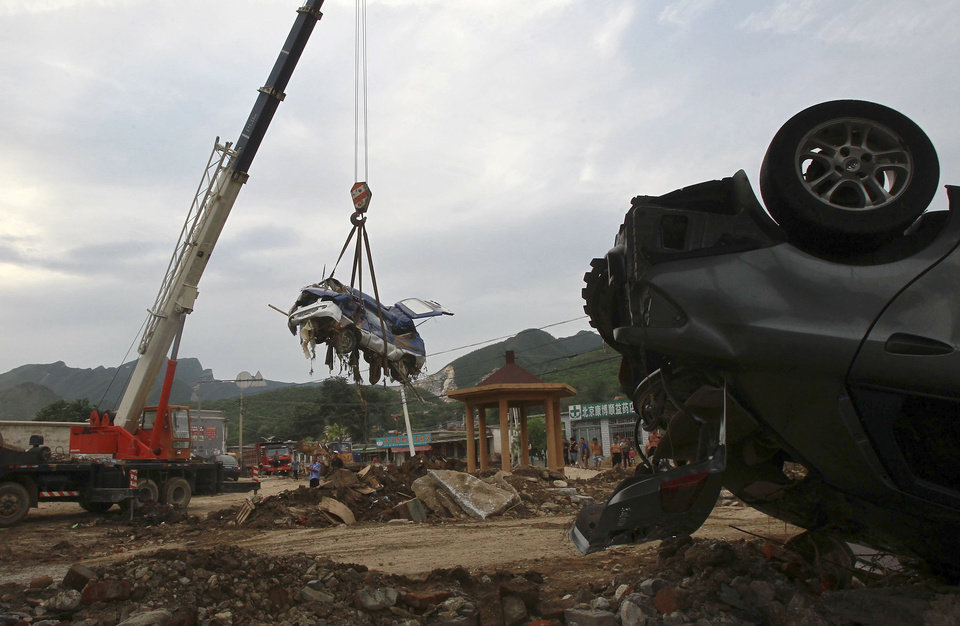 Photo -   In this photo taken on Monday, July 23, 2012, a crane lifts a damaged vehicle as workers clean up the debris following a flood in Fangshan district in Beijing. Recent heavy rains across much of China have left nearly 100 people dead, state media said Tuesday. More than a third of the fatalities were in the flood-ravaged capital, where some residents questioned whether the city's rapid push for modernization came at the expense of basic infrastructure such as drainage networks. (AP Photo) CHINA OUT