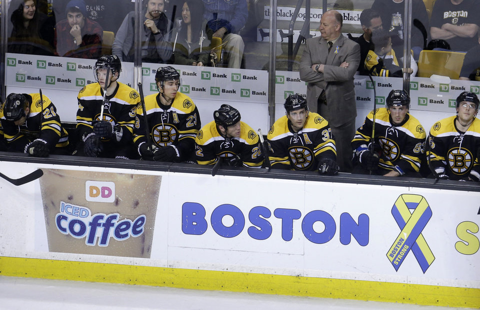 Photo - Boston Bruins head coach Claude Julien, top right, and members of the Bruins team react from the bench as they fall behind in the third period of an NHL hockey game against the Ottawa Senators at the TD Garden, in Boston, Sunday, April 28, 2013. The Senators beat the Bruins 4-2. (AP Photo/Steven Senne)