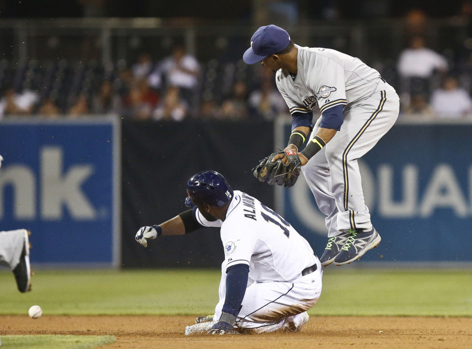 Photo - Milwaukee Brewers shortstop Jean Segura watches the ball bounce away as San Diego Padres' Abraham Almonte slides in safely after Segura committed an error failing to catch a throw from second baseman Scooter Gennett in the third inning of a baseball game Tuesday, Aug. 26, 2014, in San Diego. (AP Photo/Lenny Ignelzi)
