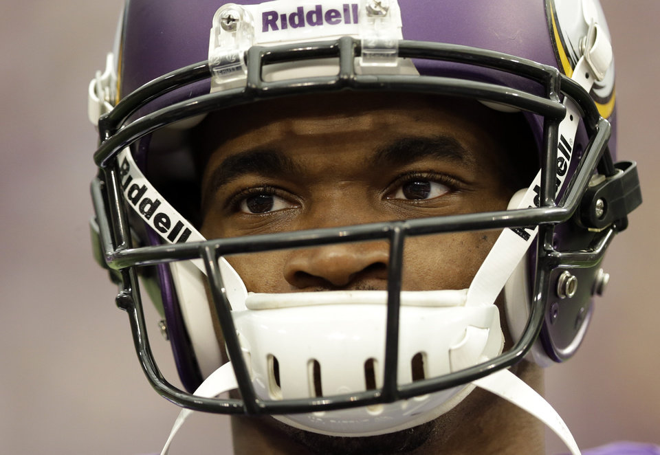 Photo - Minnesota Vikings running back Adrian Peterson pauses during introductions before an NFL football game against the Carolina Panthers in Minneapolis, Sunday, Oct. 13, 2013. One of the star running back's sons, a 2-year-old in South Dakota, died Friday after an alleged attack in a child abuse case. (AP Photo/Michael Conroy)