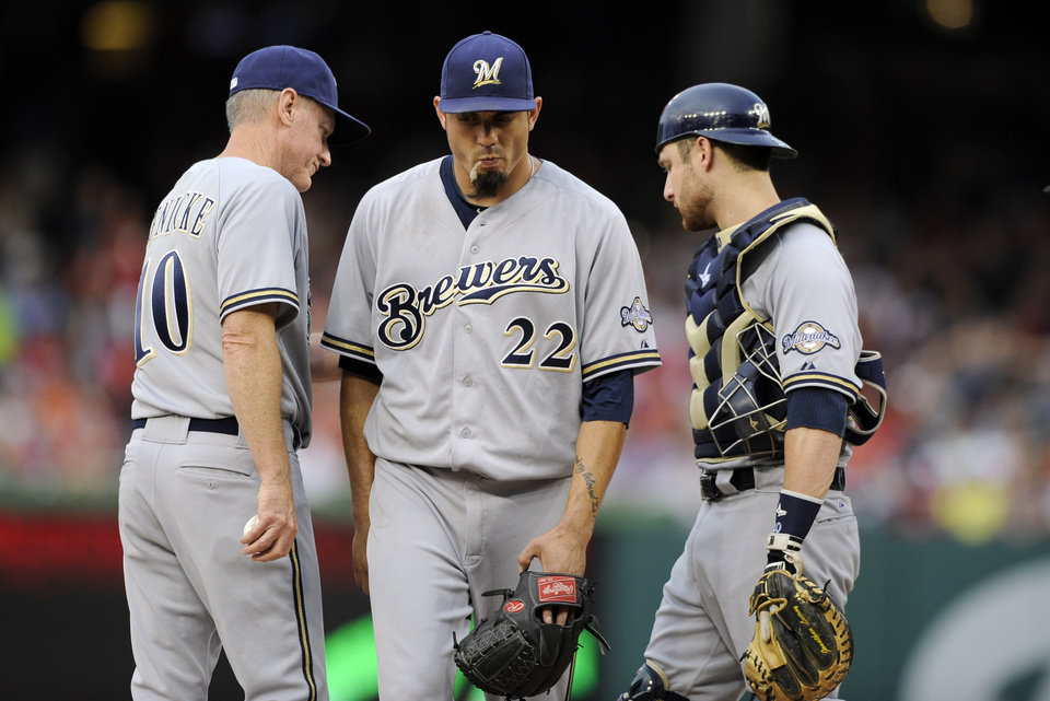 Photo - Milwaukee Brewers starting pitcher Matt Garza (22) is pulled from the baseball game against the Washington Nationals by manager Ron Roenicke (10) as catcher Jonathan Lucroy stands at right, in the first inning Saturday, July 19, 2014, in Washington. (AP Photo/Nick Wass)
