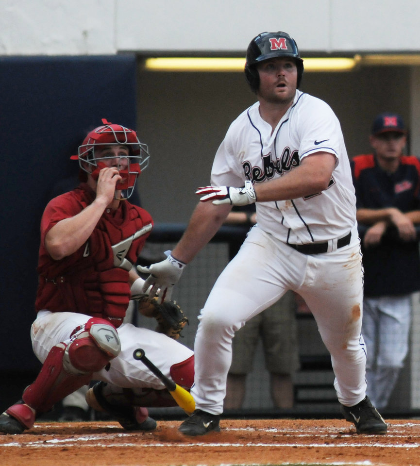 Photo - Mississippi's Sikes Orvis (24) hits an RBI double as Jacksonville State's Stephen Bartlett (33) watches at the NCAA Oxford Regional at Oxford-University Stadium on Saturday, May 31, 2014.  (AP Photo/The Oxford Eagle, Bruce Newman)