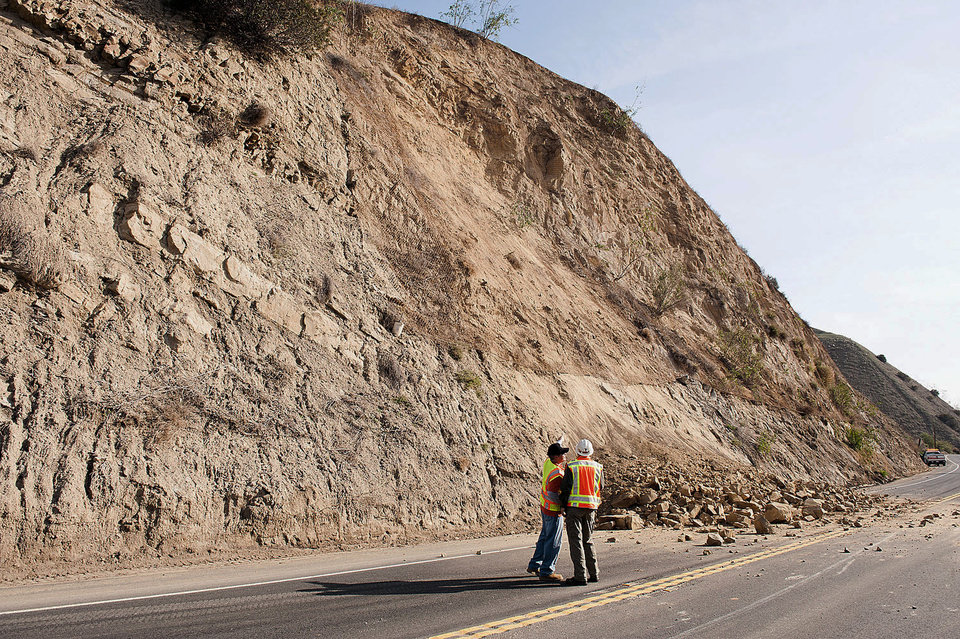 Photo - A CalTrans worker and a geologist look at a rock wall where a rockslide closed Carbon Canyon Road near Carbon Canyon Regional Park in Brea, Calif., on Saturday, March 29, 2014 after an earthquake hit Orange County Friday night. More than 100 aftershocks have rattled Orange County south of Los Angeles where a magnitude-5.1 earthquake struck Friday.  Despite the relatively minor damage, no injuries have been reported. (AP Photo/The Orange County Register, Ken Steinhardt)   MAGS OUT; LOS ANGELES TIMES OUT
