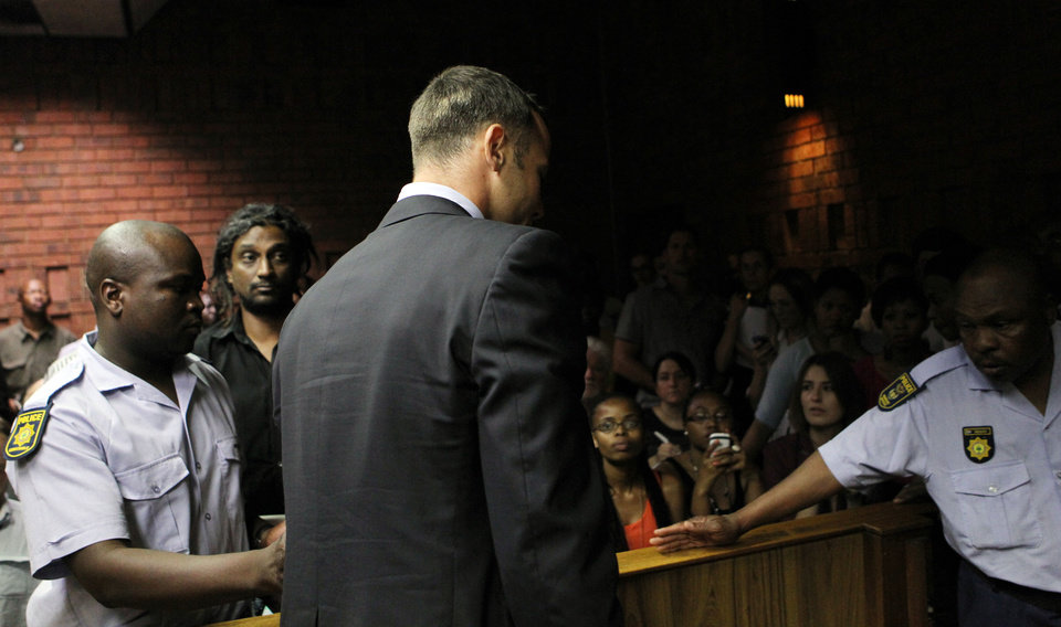 Olympic athlete Oscar Pistorius , center, is lead by police officer out of the witness bench after his bail application appearance at the magistrate court in Pretoria, South Africa, Friday, Feb. 15, 2013. Pistorius was taken into custody after a 30-year-old woman, Reeva Steenkamp, was shot dead at his home on Thursday, Feb. 14, 2013. (AP Photo/Themba Hadebe)