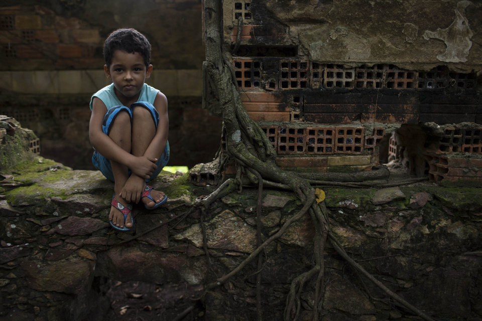 Photo - In this May 21, 2014 photo, a boy watches a soccer match as he waits for his turn to play in the ruins of Paricatuba, near Manaus, Brazil. Paricatuba was built in 1898 at the height of the region's rubber boom, which briefly transformed Manaus into one of the richest cities in the world. The sprawling villa was initially intended to house the Italian immigrants who arrived to work in the rubber trade. (AP Photo/Felipe Dana)