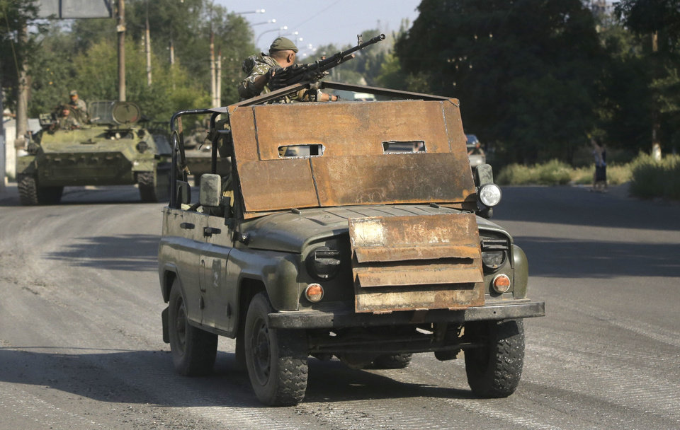 Photo - Pro-Russian rebels ride on an armored jeep in the town of Krasnodon, eastern Ukraine, Sunday, Aug. 17, 2014. A column of several dozen heavy vehicles, including tanks and at least one rocket launcher, rolled through rebel-held territory on Sunday.(AP Photo/Sergei Grits)