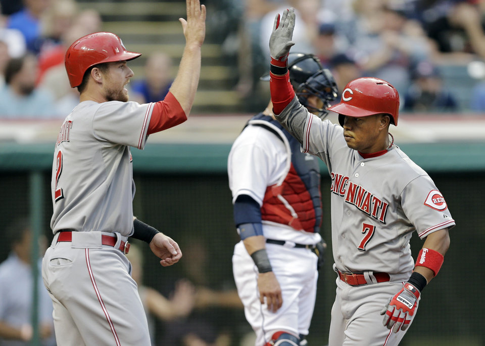 Photo - Cincinnati Reds' Ramon Santiago (7) is greeted at the plate by Zack Cozart after Santiago's three-run home run against the Cleveland Indians in the second inning of a baseball game Tuesday, Aug. 5, 2014, in Cleveland. (AP Photo/Mark Duncan)