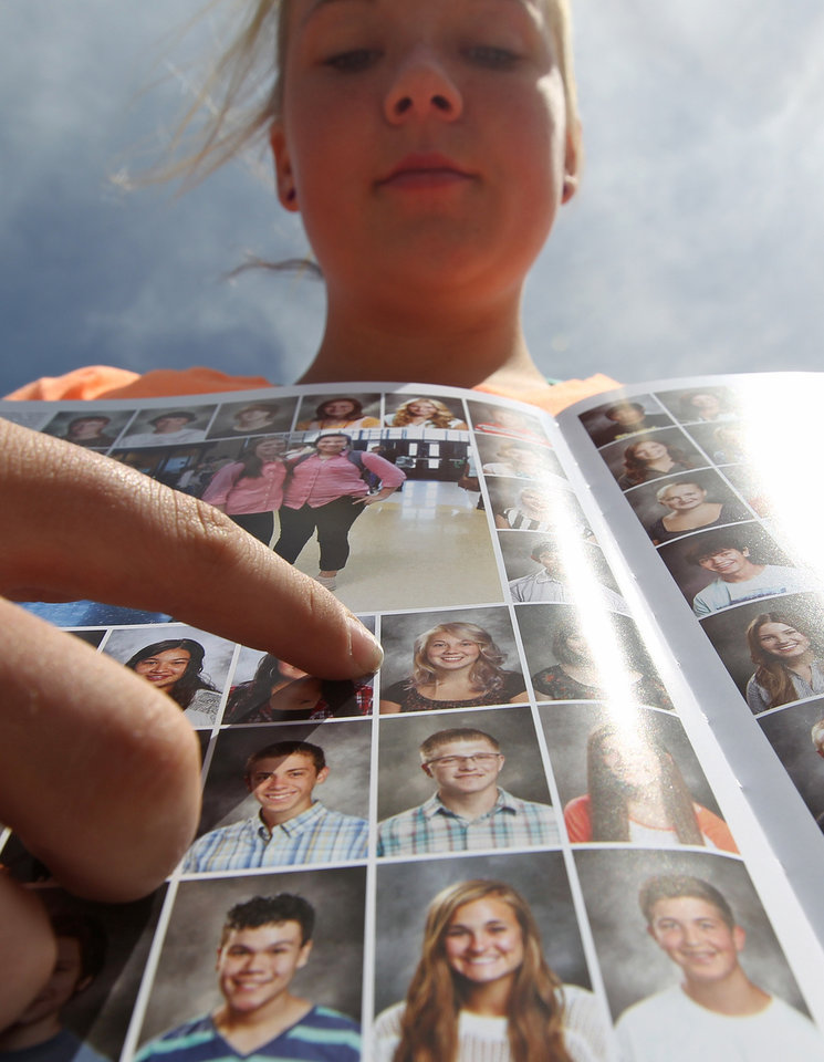 Photo - Wasatch High School sophomore Rachel Russell, 16, points to her altered school yearbook photo, center, Thursday, May 29, 2014, in Heber City, in Utah. A group of Utah high school students said they were shocked and upset to discover their school yearbook photos were digitally altered, with sleeves and higher necklines drawn on to cover up bare skin.