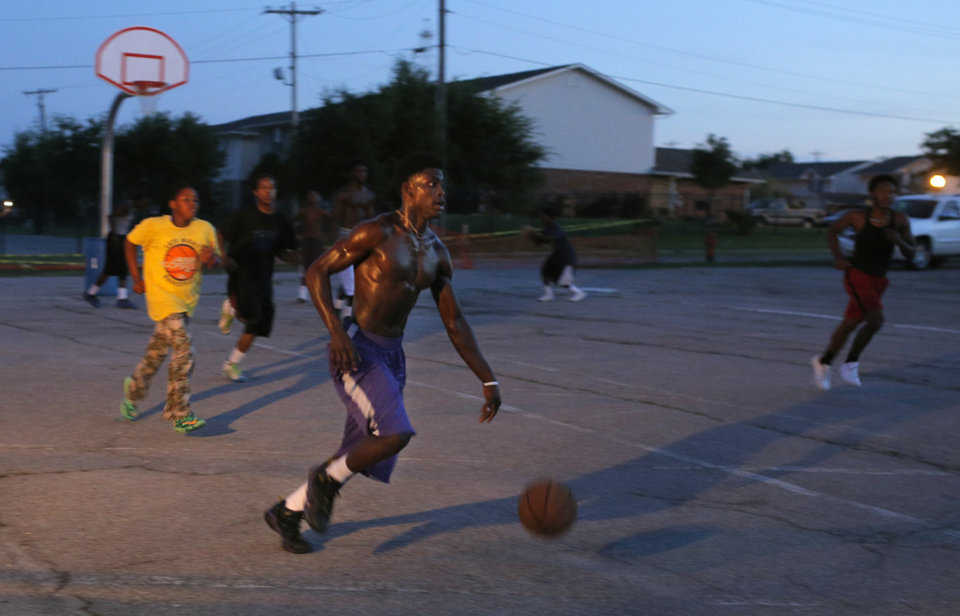 Photo - Quasean Sims dribbles up court as the sun sets during midnight basketball at Christ Temple Community Church in Oklahoma City, Friday, Aug. 1, 2014. Photo by Sarah Phipps, The Oklahoman