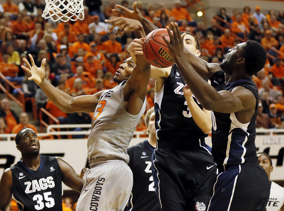 Photo - Oklahoma State's Marcus Smart (33) loses the ball against Gonzaga's Kyle Dranginis (3) and Guy Landry Edi (10) as Sam Dower (35) looks on during a men's college basketball game between Oklahoma State University (OSU) and Gonzaga at Gallagher-Iba Arena in Stillwater, Okla., Monday, Dec. 31, 2012. Photo by Nate Billings, The Oklahoman