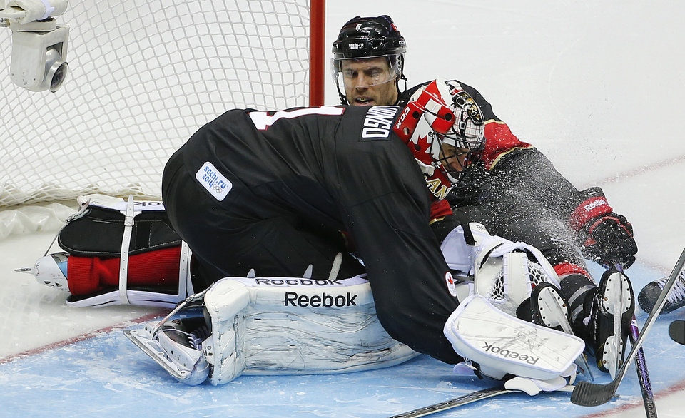 Photo - Canada goaltender Roberto Luongo smothers the puck on a rebound in the third period of a men's ice hockey game against Austria at the 2014 Winter Olympics, Friday, Feb. 14, 2014, in Sochi, Russia. (AP Photo/Julio Cortez)