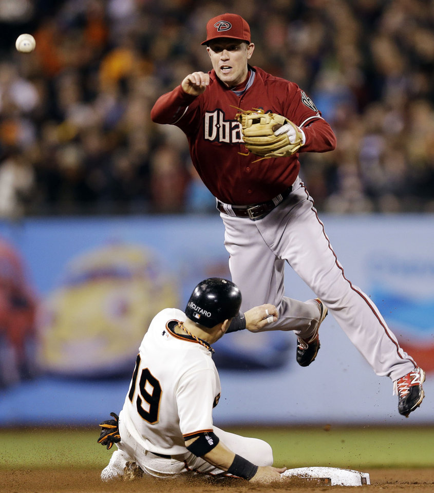Photo -   Arizona Diamondbacks second baseman Aaron Hill, top, forces out San Francisco Giants' Marco Scutaro at second base on a ground ball from Pablo Sandoval during the fourth inning of a baseball game, Wednesday, Sept. 26, 2012, in San Francisco. Sandoval was safe at first base on Hill's throw. (AP Photo/Marcio Jose Sanchez)