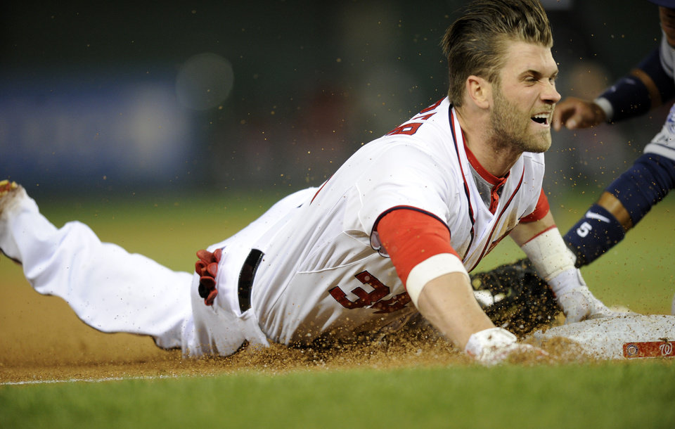 Photo - Washington Nationals left fielder Bryce Harper slides into third with  a three RBI triple during the third inning of a baseball game against the San Diego Padres, Friday, April 25, 2014, in Washington. (AP Photo/Nick Wass)