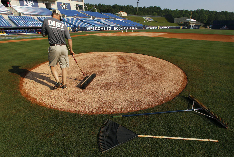 Photo - In this May 22, 2014 photo, Justin Marlin, of Trussville, Ala.,  rakes the pitcher's mound at the Southeastern Conference NCAA college baseball tournament in Hoover, Ala. (AP Photo/Butch Dill)