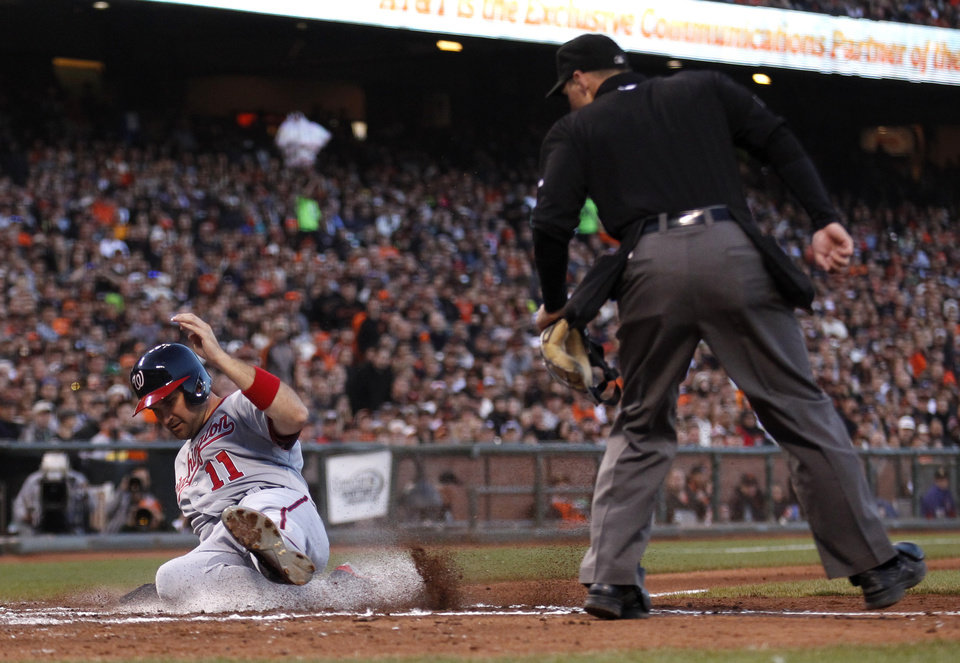 Photo - Washington Nationals' Ryan Zimmerman slides safe into home to score a run during the third inning of a baseball game against the San Francisco Giants, Monday, June 9, 2014, in San Francisco. (AP Photo/Beck Diefenbach)