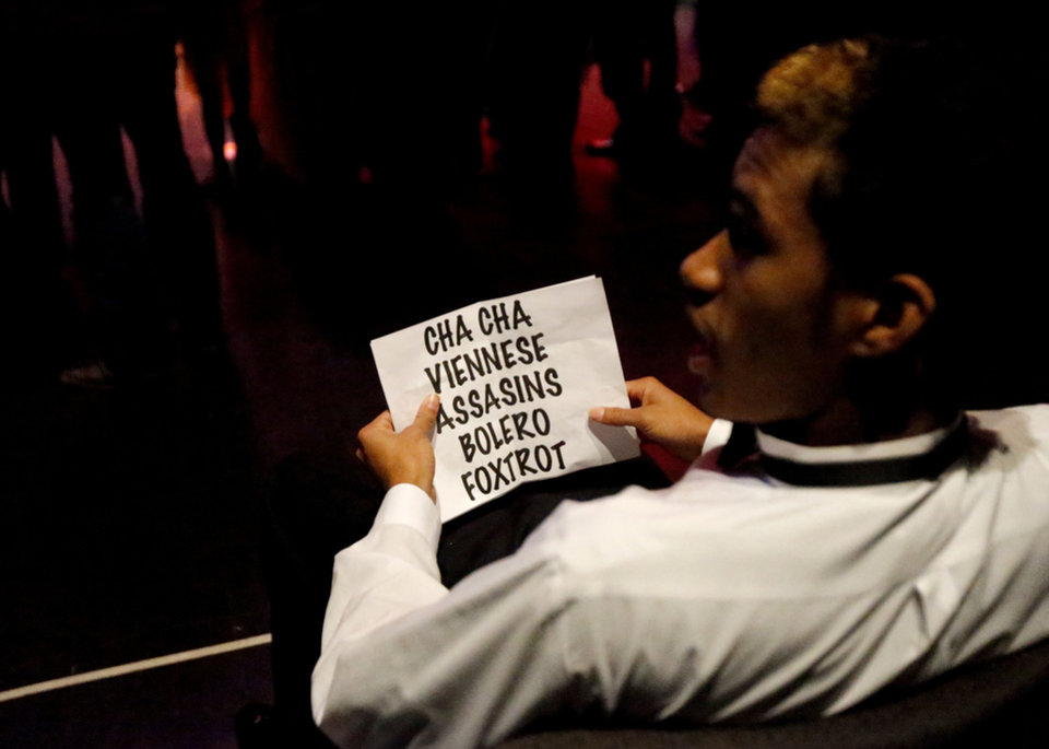 Photo - James Cotton, 17, of John Marshall High School, looks over a list of dances.