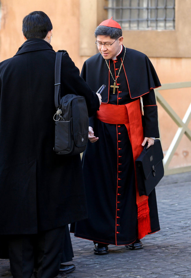 Photo - Cardinal Luis Antonio Tagle, of the Philippines, right, arrives for a meeting, at the Vatican, Monday, March 4, 2013. Cardinals from around the world have gathered inside the Vatican for their first round of meetings before the conclave to elect the next pope, amid scandals inside and out of the Vatican and the continued reverberations of Benedict XVI's decision to retire. (AP Photo/Andrew Medichini)