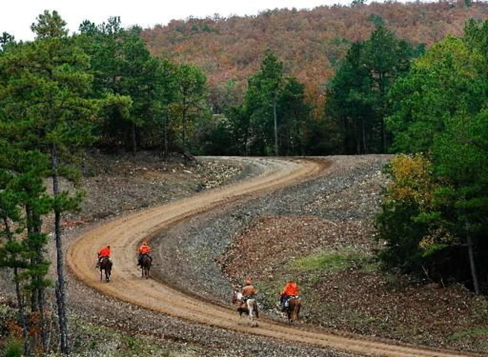 Photo - Searchers on horseback make their way up a winding, muddy road on the mountain. Law enforcement officers and volunteers converged in the small southeast Oklahoma community of Red Oak on Friday, Oct. 23, 2009, to search a heavily wooded area in the Sansbois Mountains for a missing family of three. Searches on horseback, on foot, on ATVs and in airplanes and helicopters scoured the area for any traces of the family. Oct. 21, 2009. Photo by Jim Beckel