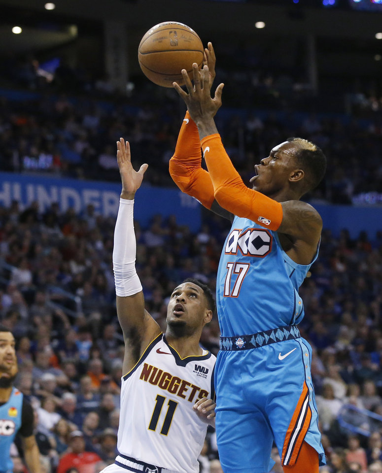 Photo - Oklahoma City Thunder guard Dennis Schroeder (17) passes the ball in front of Denver Nuggets guard Monte Morris (11) during the second half of an NBA basketball game Friday, March 29, 2019, in Oklahoma City. (AP Photo/Sue Ogrocki)