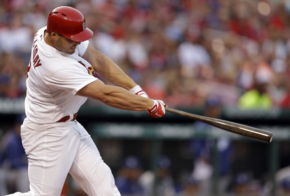Photo - St. Louis Cardinals' Matt Holliday follows through on an RBI double during the first inning of a baseball game against the Los Angeles Dodgers Friday, July 18, 2014, in St. Louis. (AP Photo/Jeff Roberson)