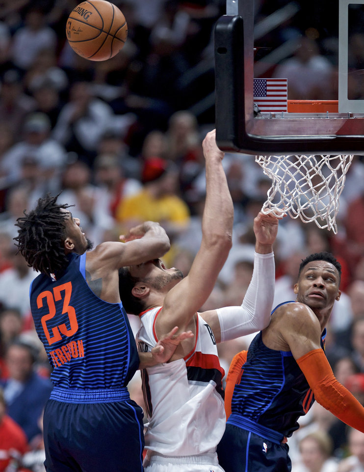 Photo - Portland Trail Blazers center Enes Kanter, center, Oklahoma City Thunder guard Terrance Ferguson, left, and guard Russell Westbrook, right, vie for a rebound during the first half of Game 5 of an NBA basketball first-round playoff series, Tuesday, April 23, 2019, in Portland, Ore. (AP Photo/Craig Mitchelldyer)
