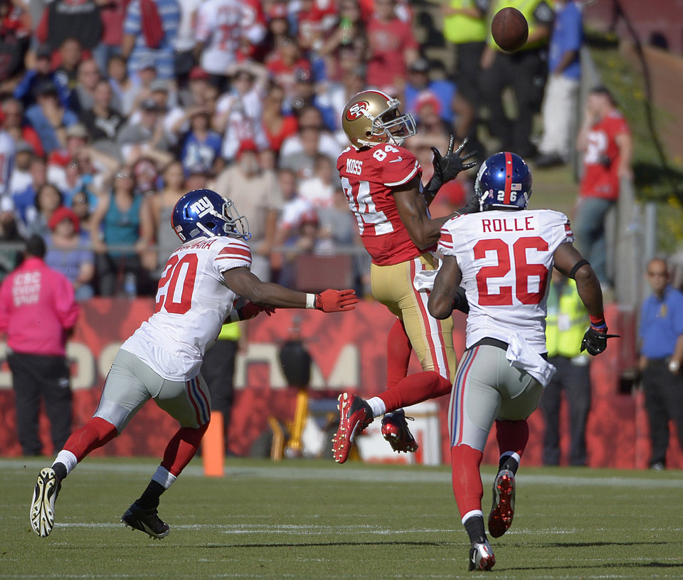 Photo -   San Francisco 49ers wide receiver Randy Moss (84) catches a pass over New York Giants cornerback Prince Amukamara (20) and free safety Antrel Rolle (26) during the third quarter of an NFL football game in San Francisco, Sunday, Oct. 14, 2012. (AP Photo/Mark J. Terrill)