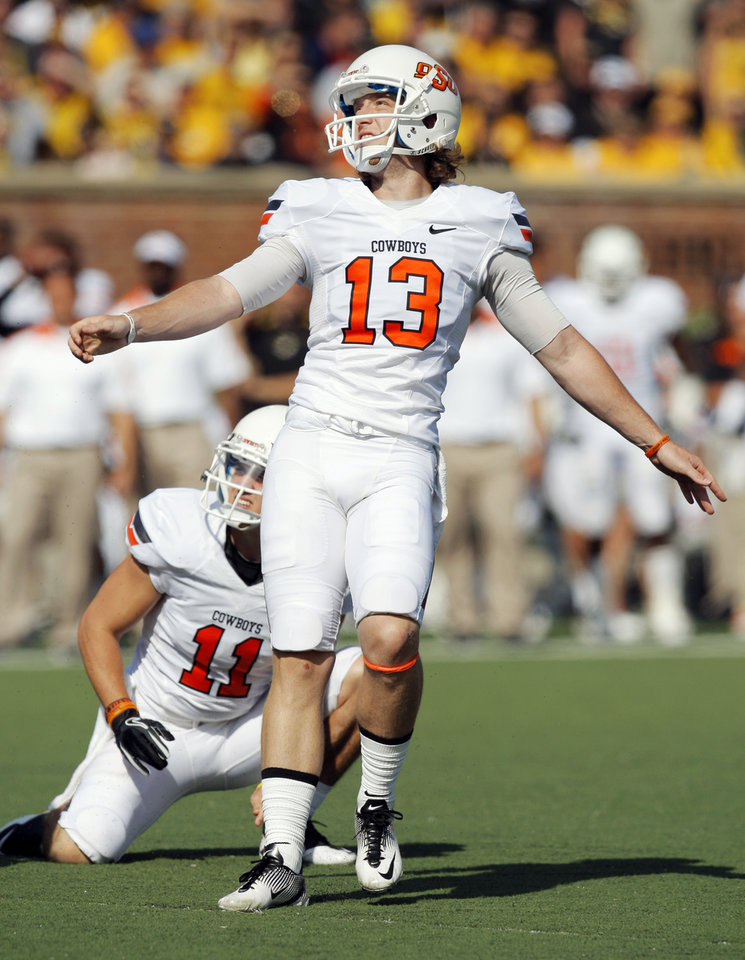 Photo - Oklahoma State's Quinn Sharp (13) watches his field goal attempt in front of holder Wes Harlan (11) in the second quarter during a college football game between the Oklahoma State University Cowboys (OSU) and the University of Missouri Tigers (Mizzou) at Faurot Field in Columbia, Mo., Saturday, Oct. 22, 2011. The field goal was good. Photo by Nate Billings, The Oklahoman